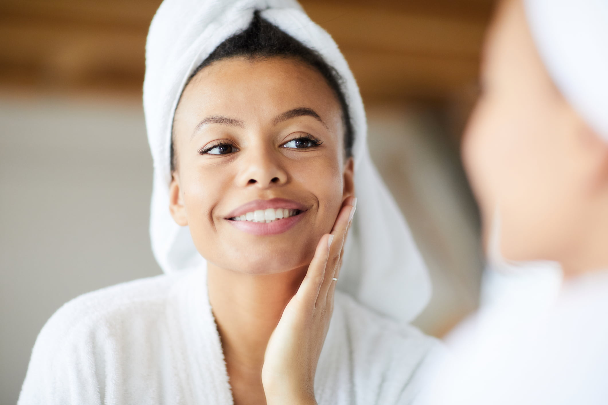 A lady is looking at the mirror and applying skincare products after showering