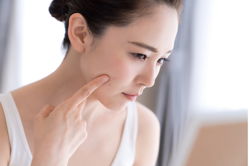 A pretty Asian woman is using her finger to touch her face