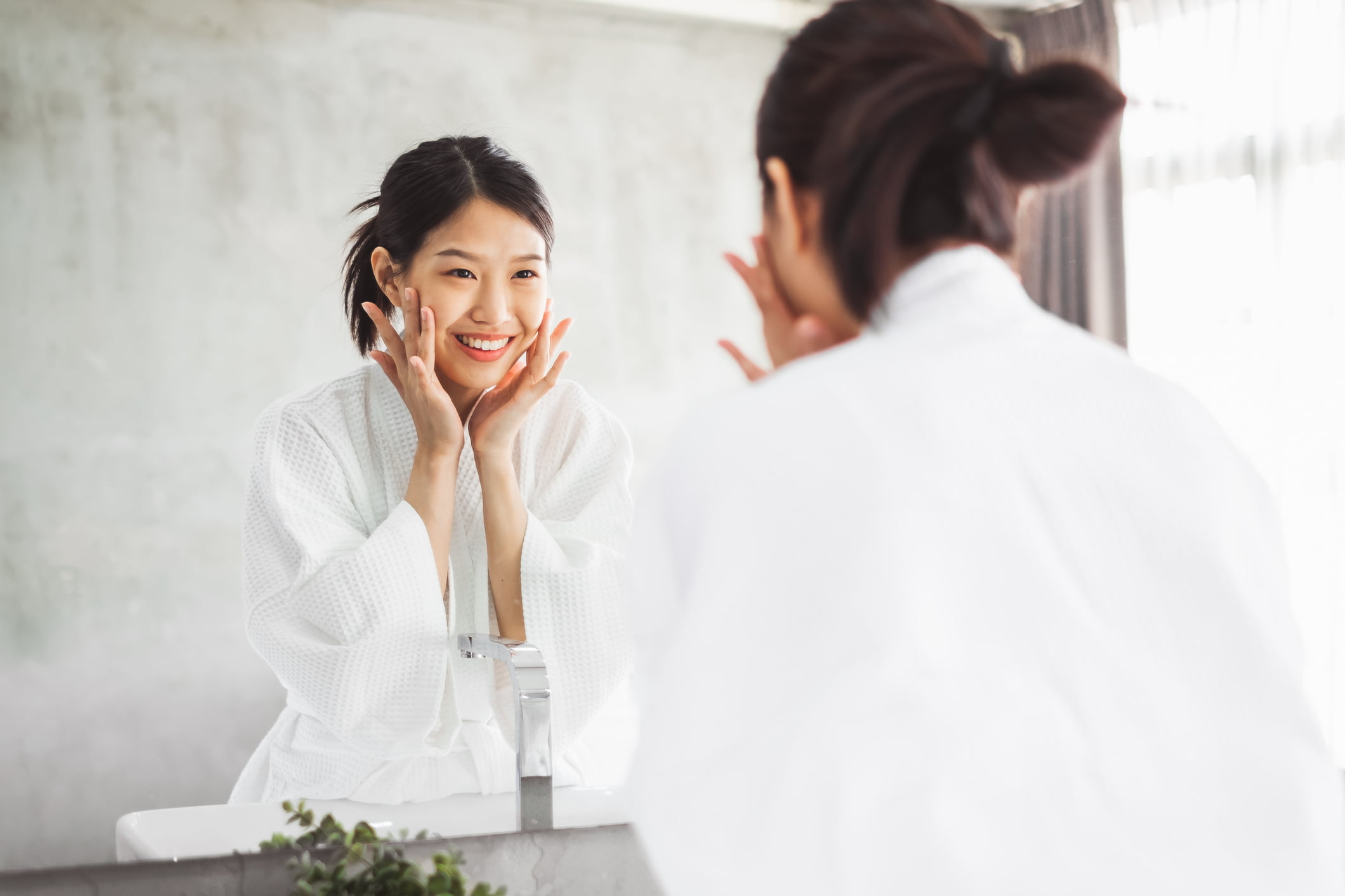 An Asian lady is looking at the mirror and applying skincare product