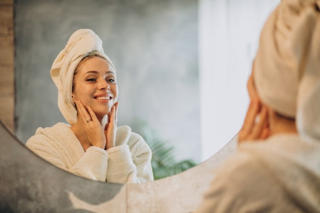 A woman is looking at the mirror and applying facial cream