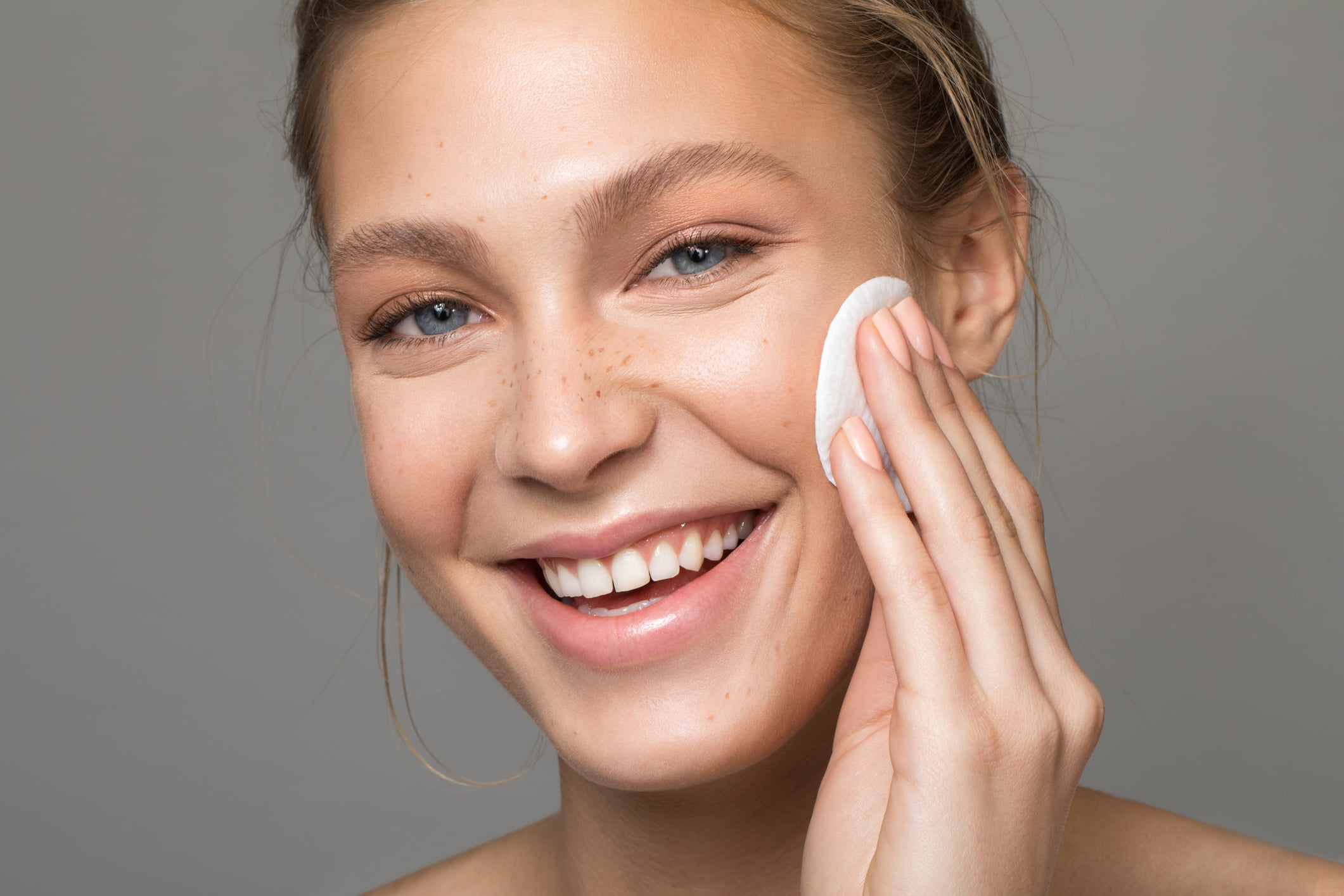 A pretty woman is applying a skincare product on her face