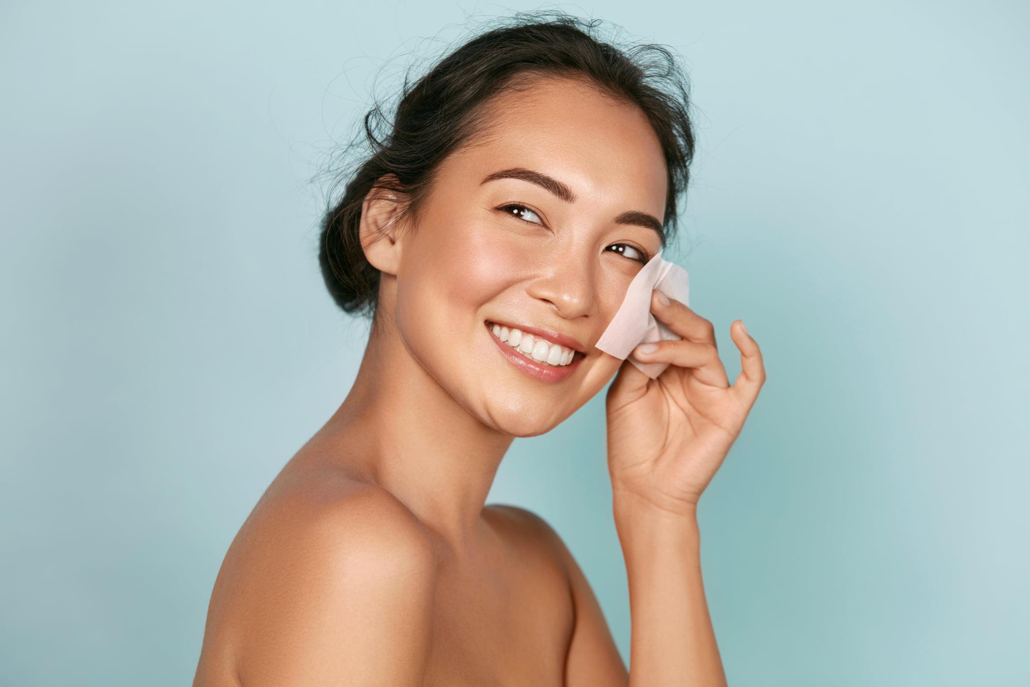 Smiling woman using facial oil blotting paper