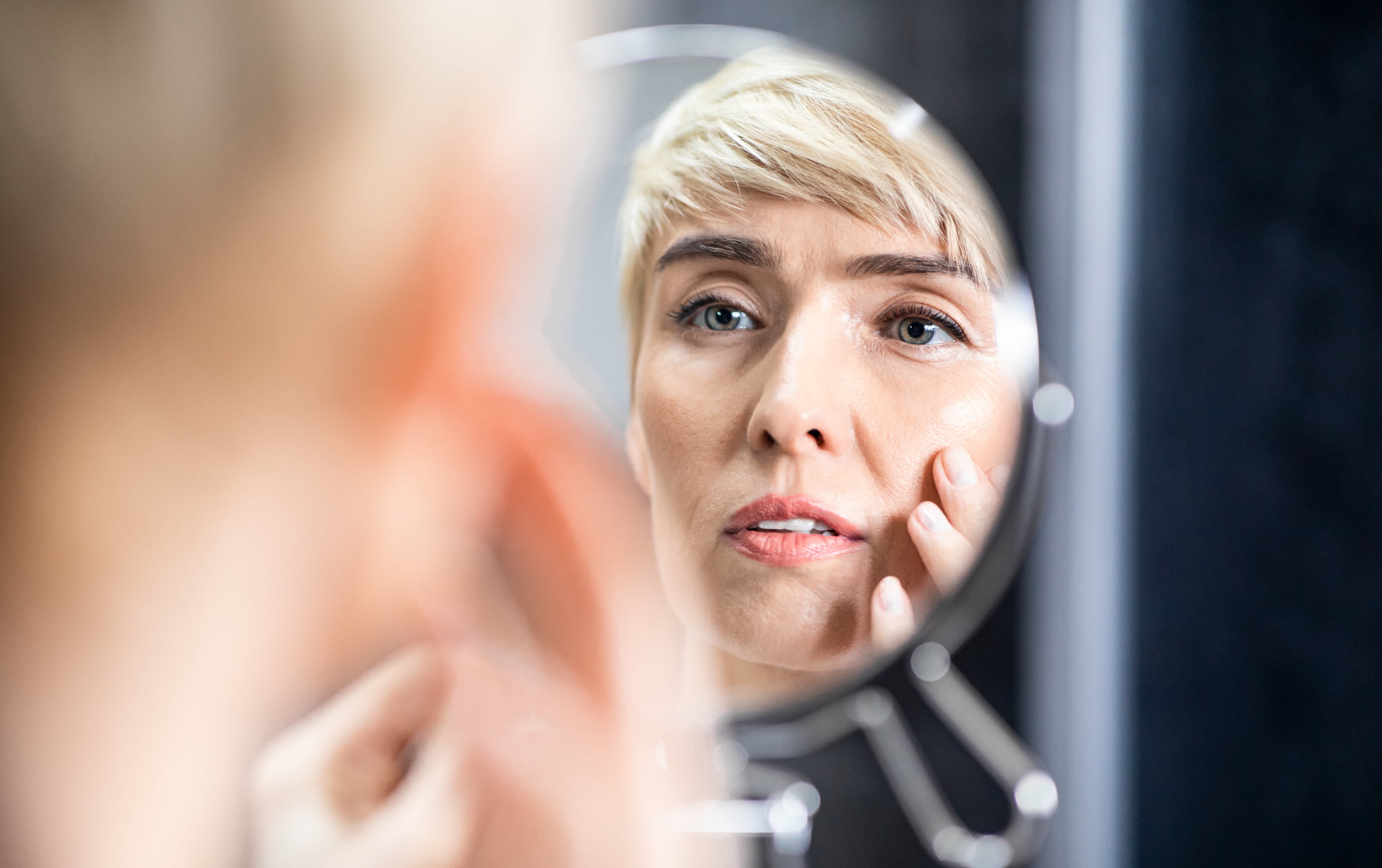 Woman looking in the mirror at wrinkles on her face.
