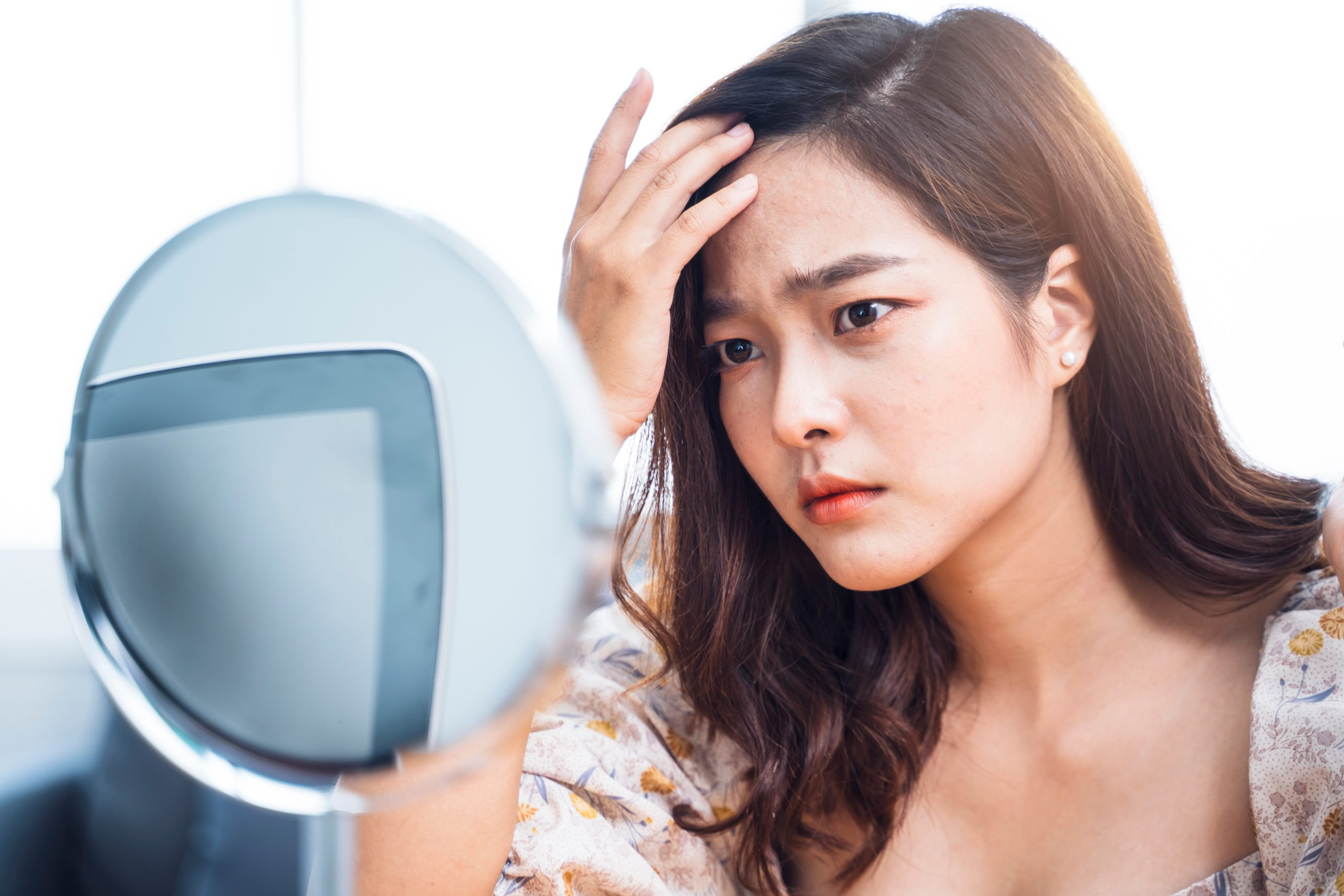 Woman looking at mirror with acne scar concern